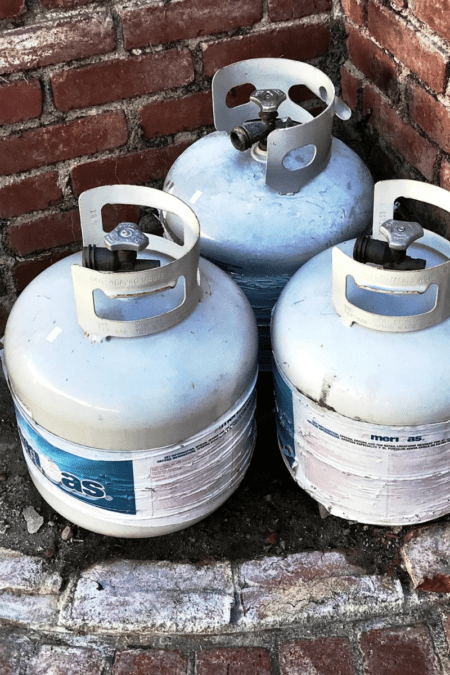 propane tanks stored in the brick fire pit for winter