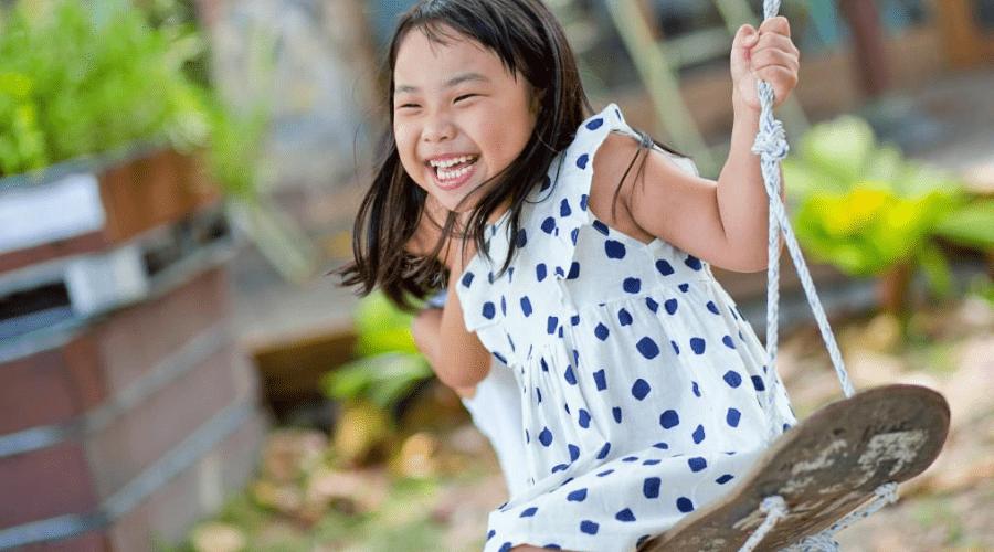 girl swinging on backyard playset