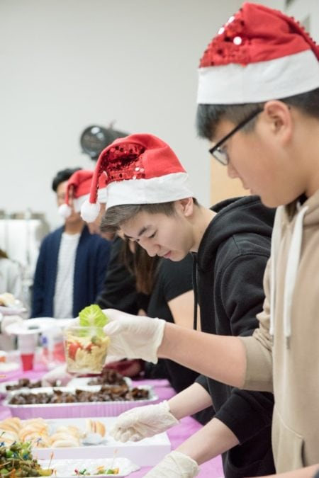 volunteer servers at community Christmas event in santa hats