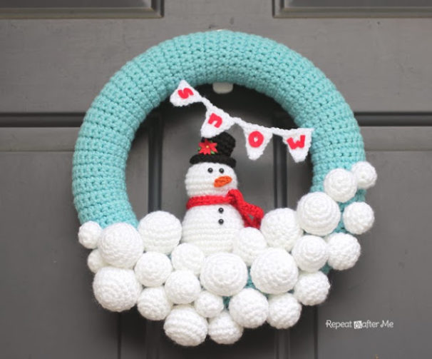 Crocheted wreath with a snowman sitting on top of snowballs and a blue arc covering the two.