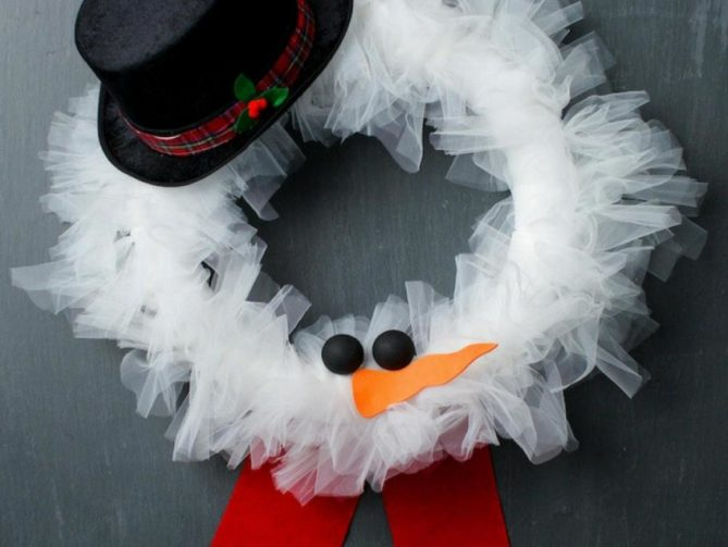 A DIY tulle wreath with eyes, nose, a black hat, and red scarf.