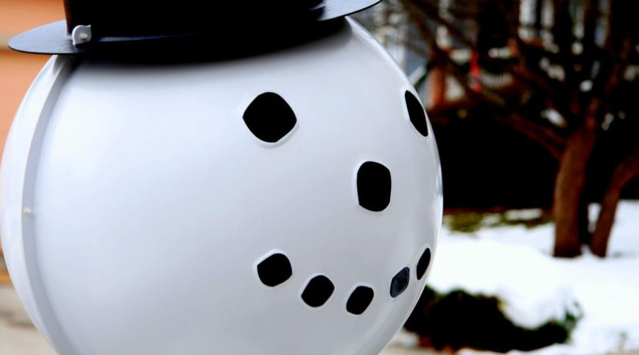 Smiling metal snowman head with black hat.