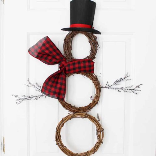 A DIY snowman wreath made from grapevine wreaths, holly leaves, and paper mache.