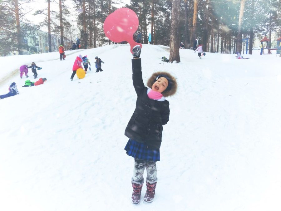 kids sledding and girl cheering with sled