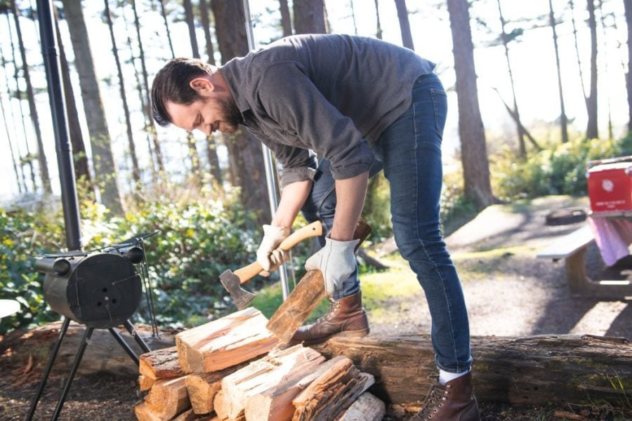 a man cutting firewood into smaller kindling