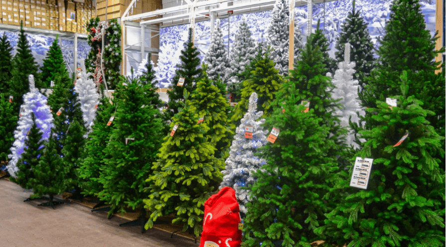 an array of artificial christmas trees in a home goods store for purchase