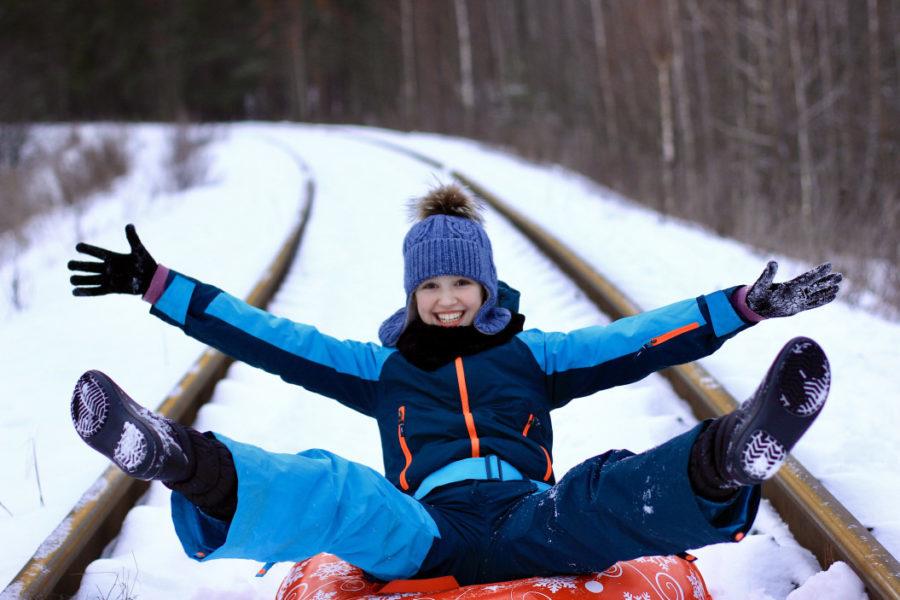 girl in snowsuit sledding down tracks in winter