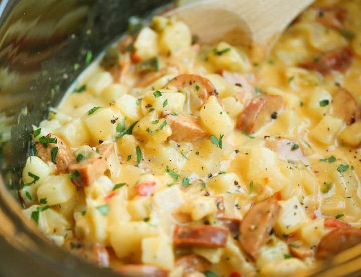 Spoon stirring delicious cheesy breakfast potatoes