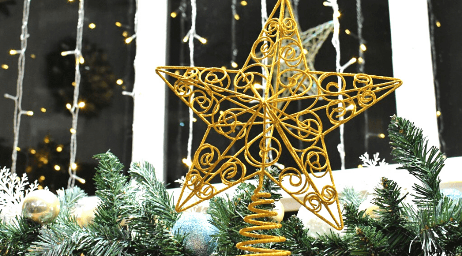 a gold wire star christmas tree topper closeup in winter setting