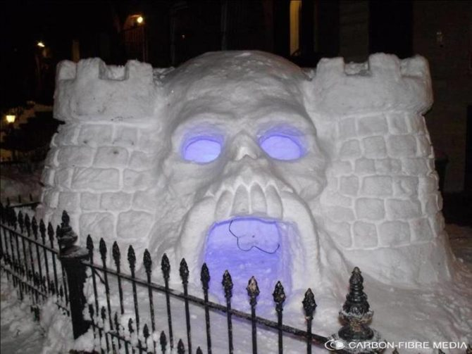A skull-shaped snow fort with purple glowing eyes and mouth.