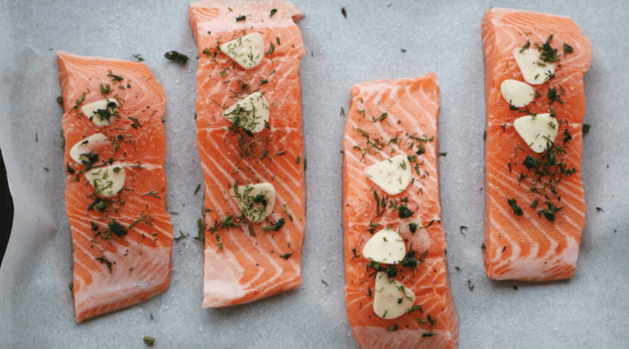 portions of salmon on parchment lined sheet with herbs lemon and garlic
