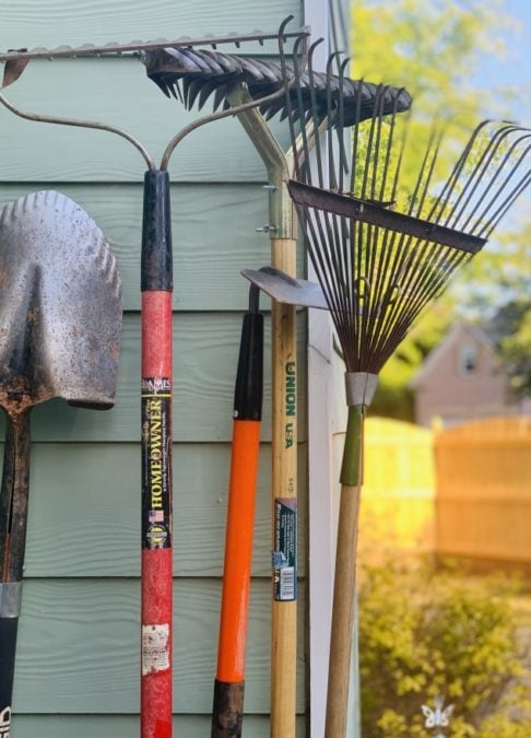 leaf raking tools rake shovel hoe leaning on side of house siding