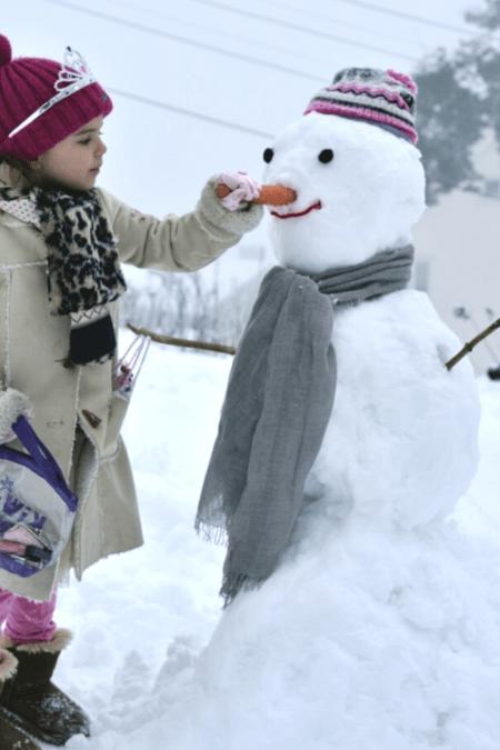 girl building a snowman outdoors winter
