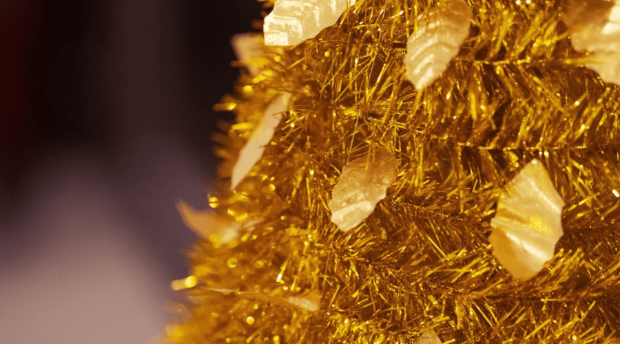 closeup of artificial christmas tree made of gold tinsel and strung with gold leaf-shaped sequins