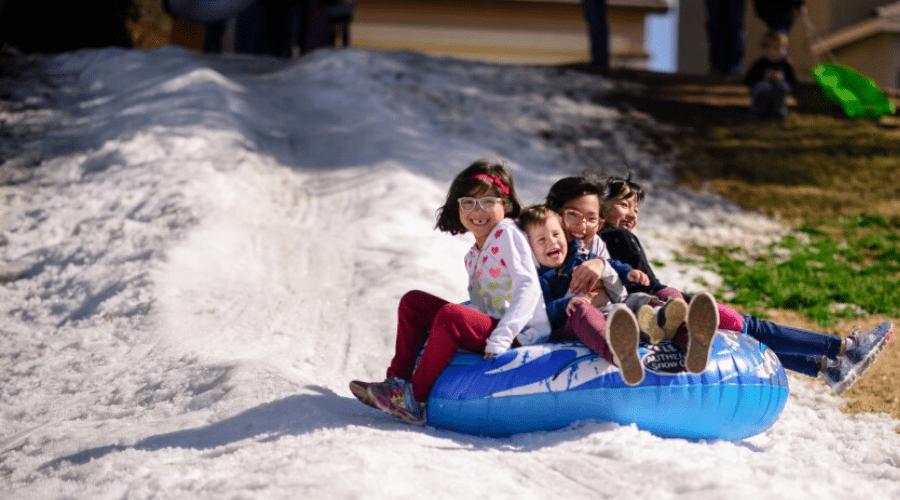 kids snow tubing ouside in melting snow on blue tube