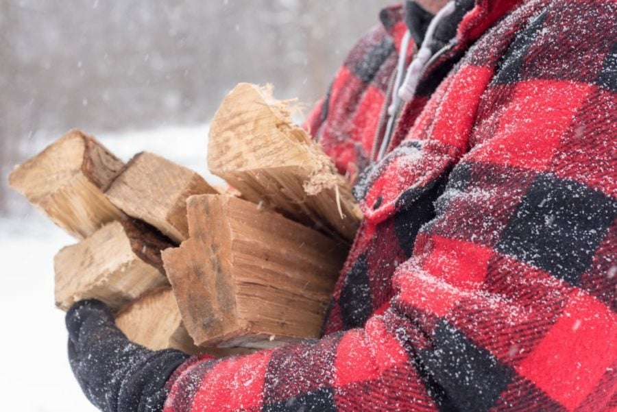 a man carrying firewood in the snow wearing a plaid jacket