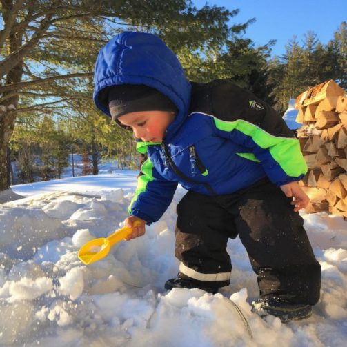 kid shoveling snow with snow toy shovel in winter