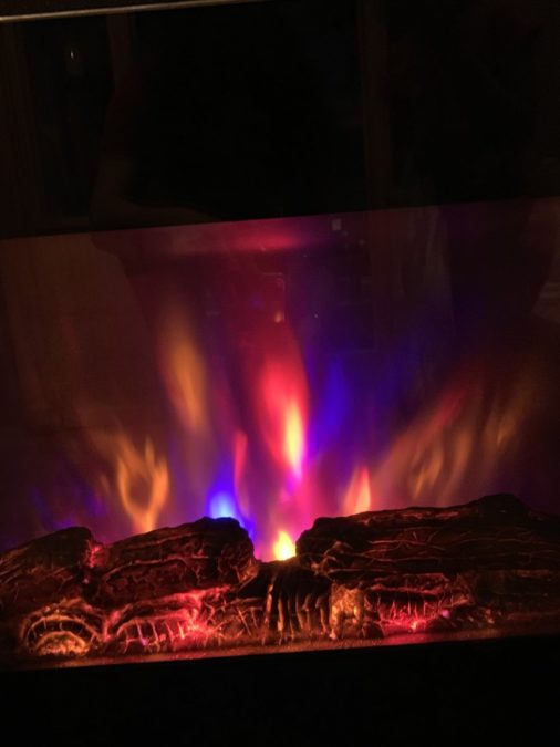 electric fireplace with bright flames in dark room