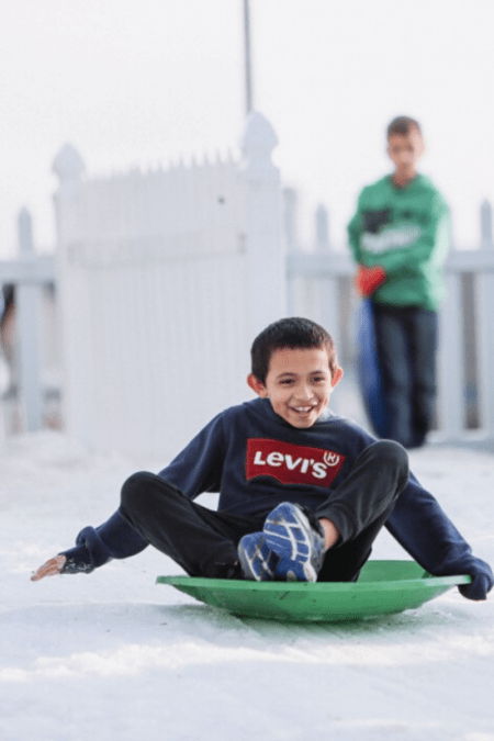 a boy sleds down a snowy hill in plastic saucer