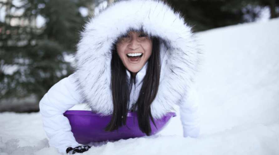 sledding woman smiling in winter