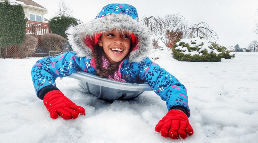 closeup of a girl on a sled head first behind house