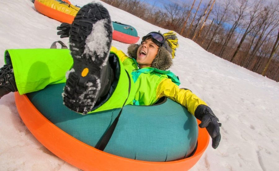 snow tube race snow games boy in snow tube racing down snowy hill