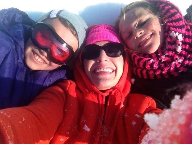family selfie on sledding hill snow day