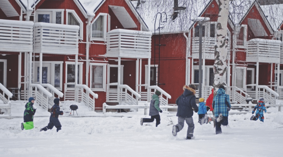 kids running playing snow games outdoors in snow in front of rowhouses