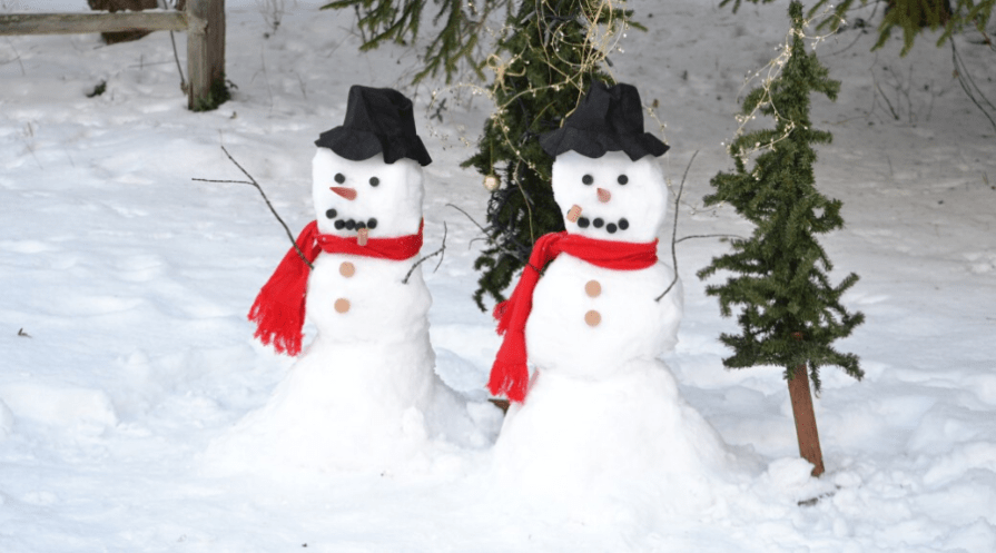 two snowmen in the snow with scarves and hats