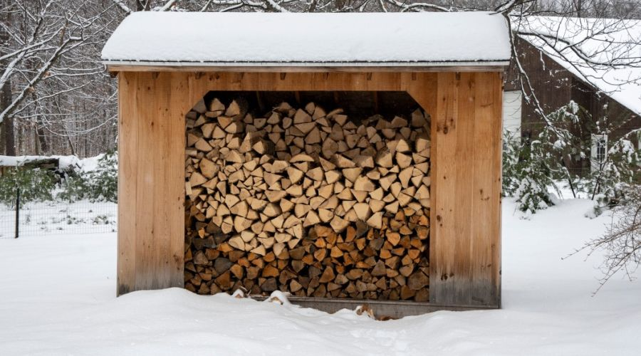A wooden shed with an open front, loaded with firewood, set in a winter wonderland.