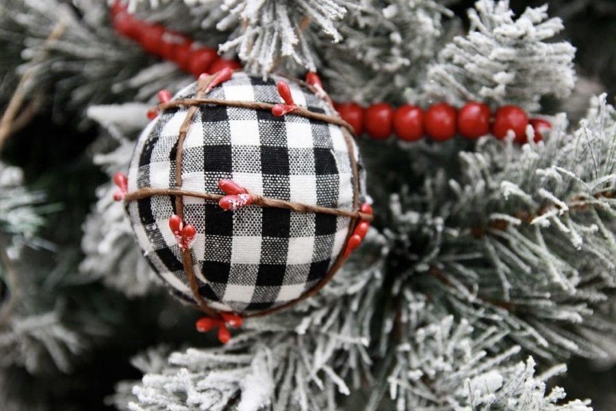 buffalo plaid christmas ornament close up on white flocked christmas tree
