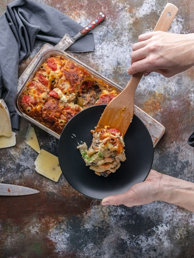 baked gratin cheese root vegetables tomatoes in casserole serving with wooden spatula