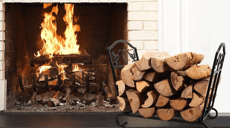 a decorative firewood rack full of logs by a lighted fireplace indoors