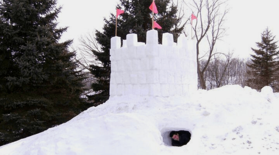 a man in the tunnel below a two-story snow fort with pink flags