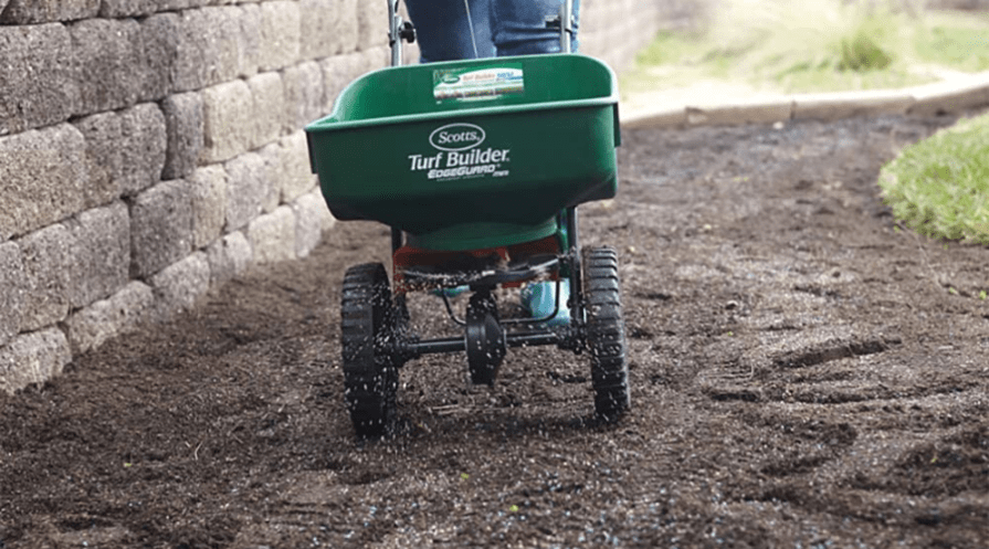 turfbuilder broadcast spreader in use over soil path