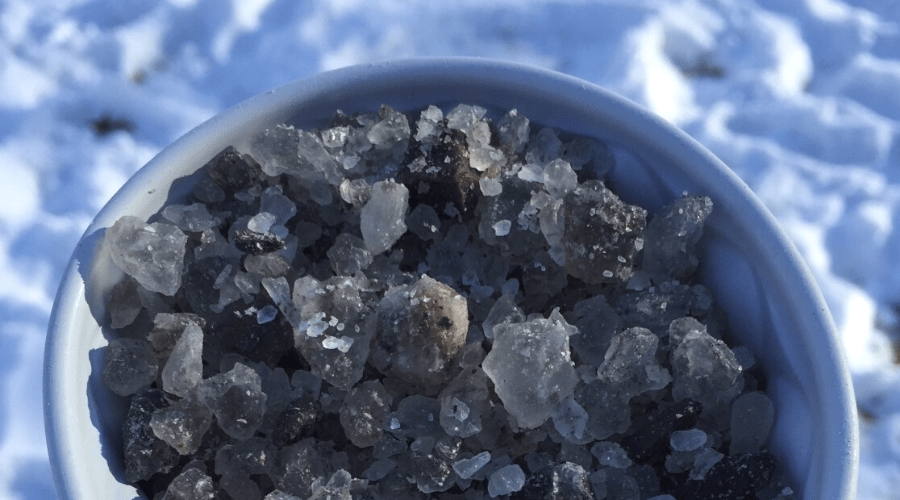 gray rock salt in a bowl outdoors in snow