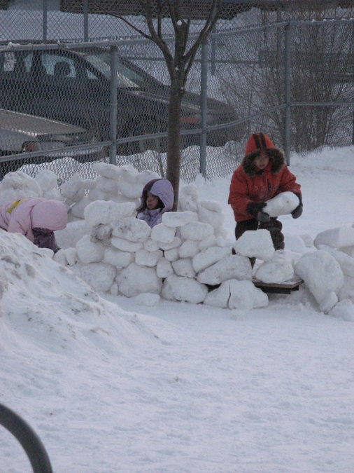 kids using hard blocks of snow to build a fort