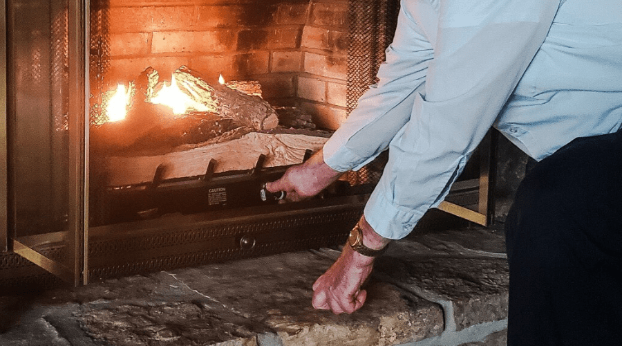 Older man is an active senior who is adjusting his gas logs after turning them on in the winter for warmth and comfort in his home