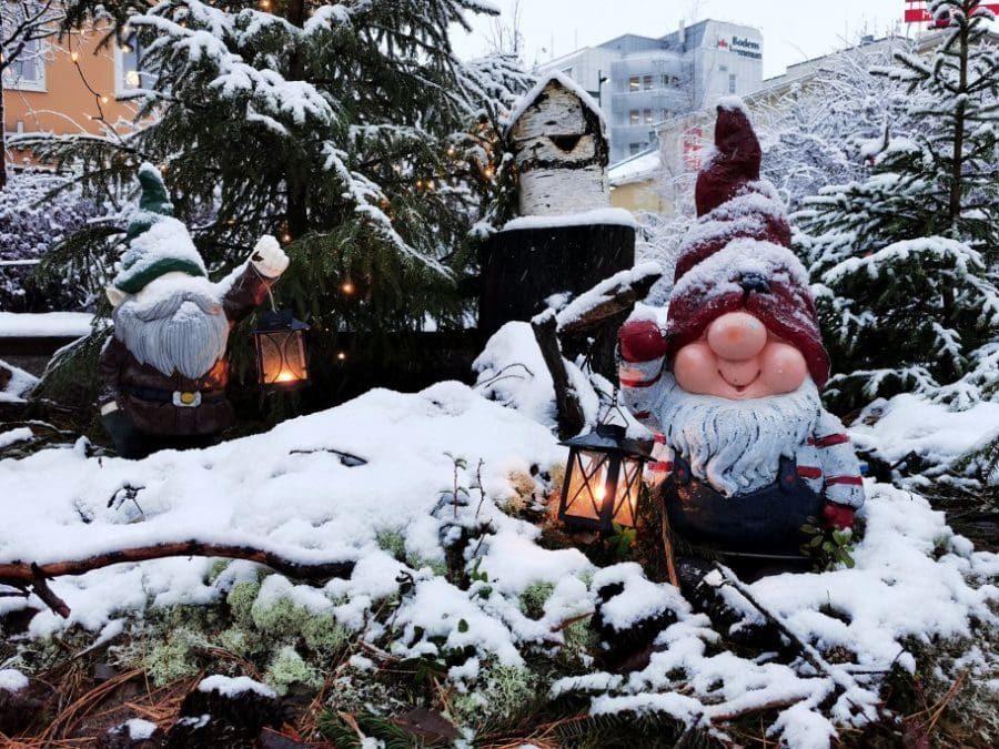 christmas gnome in red hat outdoors in snow carrying lantern