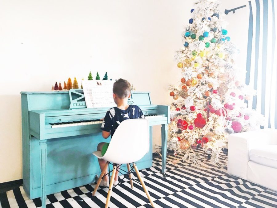 colorful christmas tree in room with blue piano