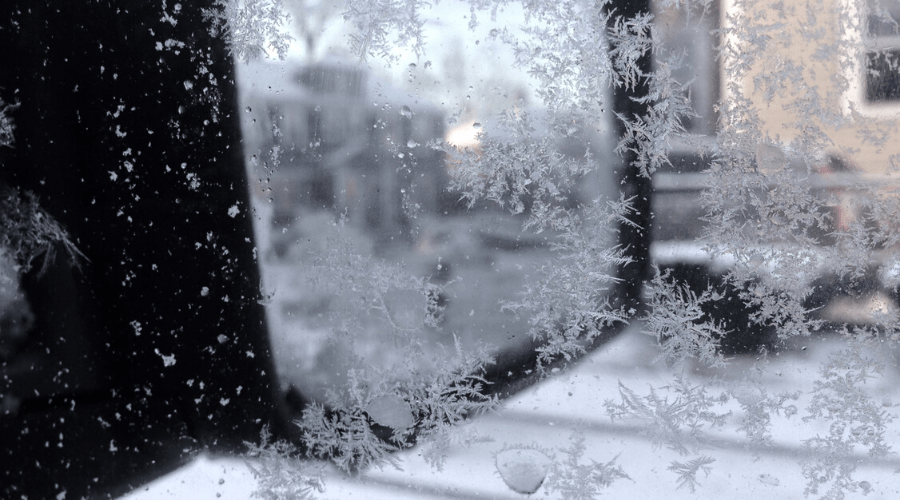 snowflakes and ice on a car window with the mirror and a house in the background through a window in winter