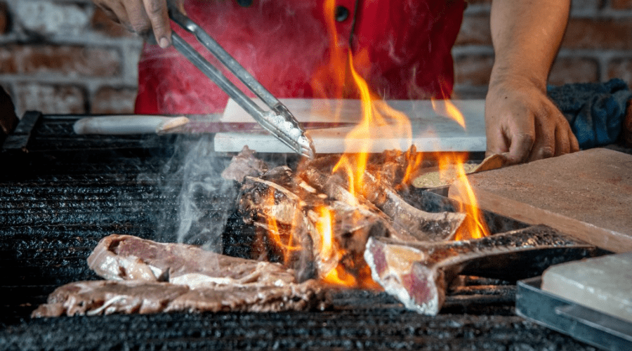 grill gifts xmas featured man cooking meat on hot grill with tongs