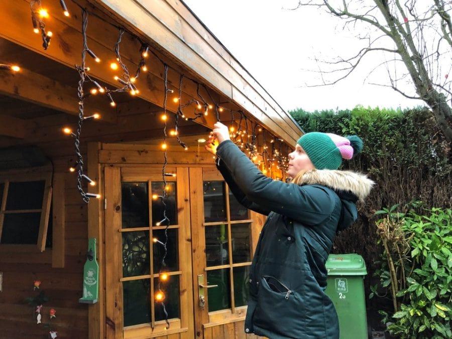 woman hanging christmas lights on home exterior
