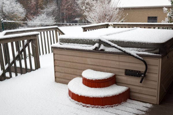 Covered hot tub on a residential porch in a snow storm
