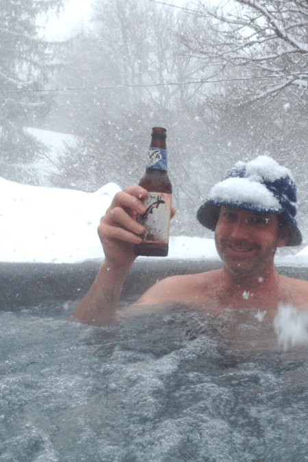hot tub winter guide tall man in hot tub snowfall winter hat holding beer