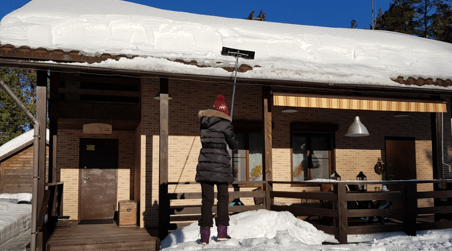 woman clears snow from one-story home with low pitch roof