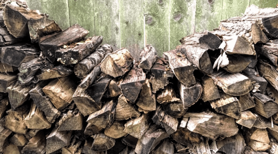 a stack of split and seasoned firewood against a fence outdoors