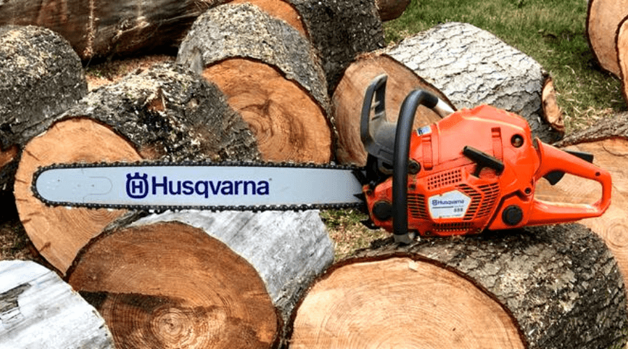 husqvarna 555 2020 review wide glamor shot chainsaw atop a neat stack of clean cut logs wide diameter