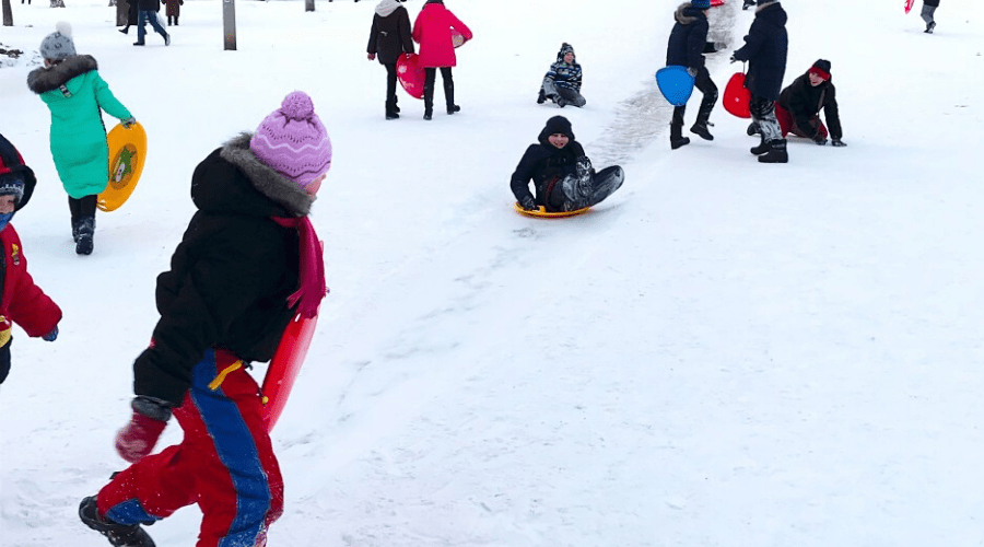 kids sledding on hill in snow in diffferent types sled