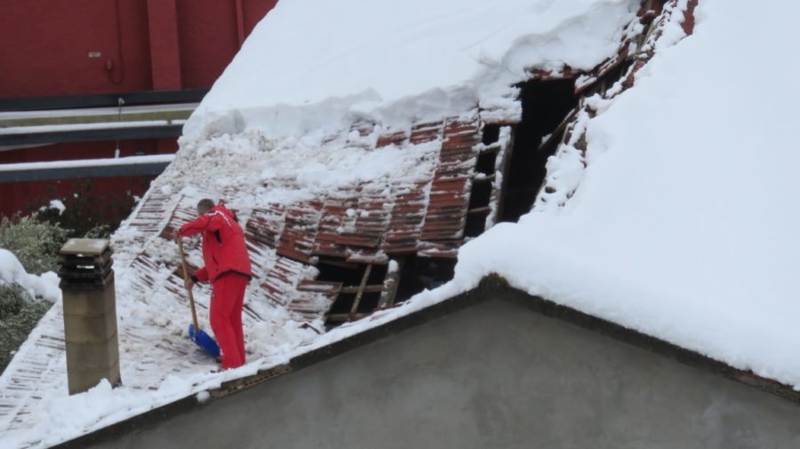 man on collapsed roof for snow ice dam prevention extensive damage